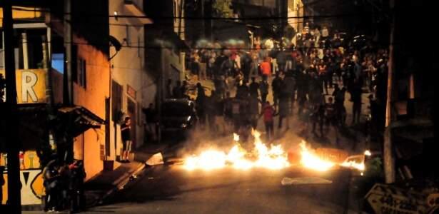 Foto retrata um protesto com um incêndio