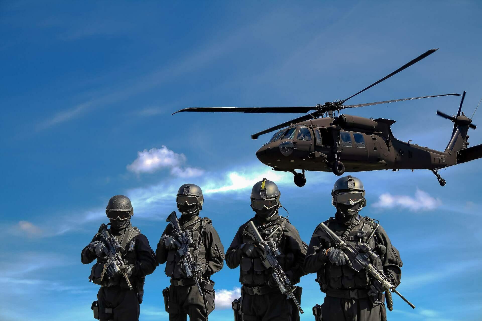 Imagem ilustrativa sobre o tema de intervenção militar internacional. Militares acompanhados de um helicoptero militar (Fonte: Pixabay)