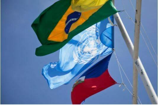 Bandeira do Brasil junto à bandeira das Nações Unidas e do Haiti.