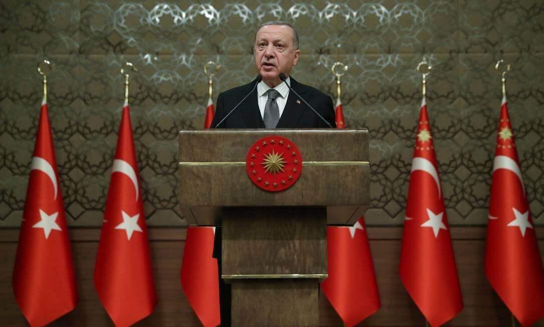 Na imagem, presidente da Turquia em pé, durante discurso, rodeado de bandeiras do país.
