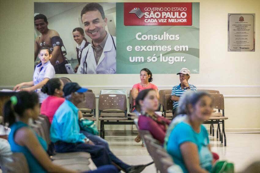 Na imagem, pessoas sentadas esperando em uma sala de espera de hospital. Conteúdo sobre Judicialização da saúde no Brasil.