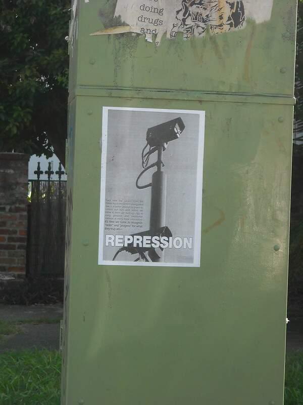 Na imagem, um cartaz escrito Repression com a figura de uma camera de vigilância. Conteúdo sobre as principais violações de direitos humanos.