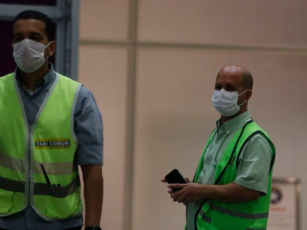 Funcionários do aeroporto com máscaras de cirurgia. Conteúdo sobre Estado de Emergência.