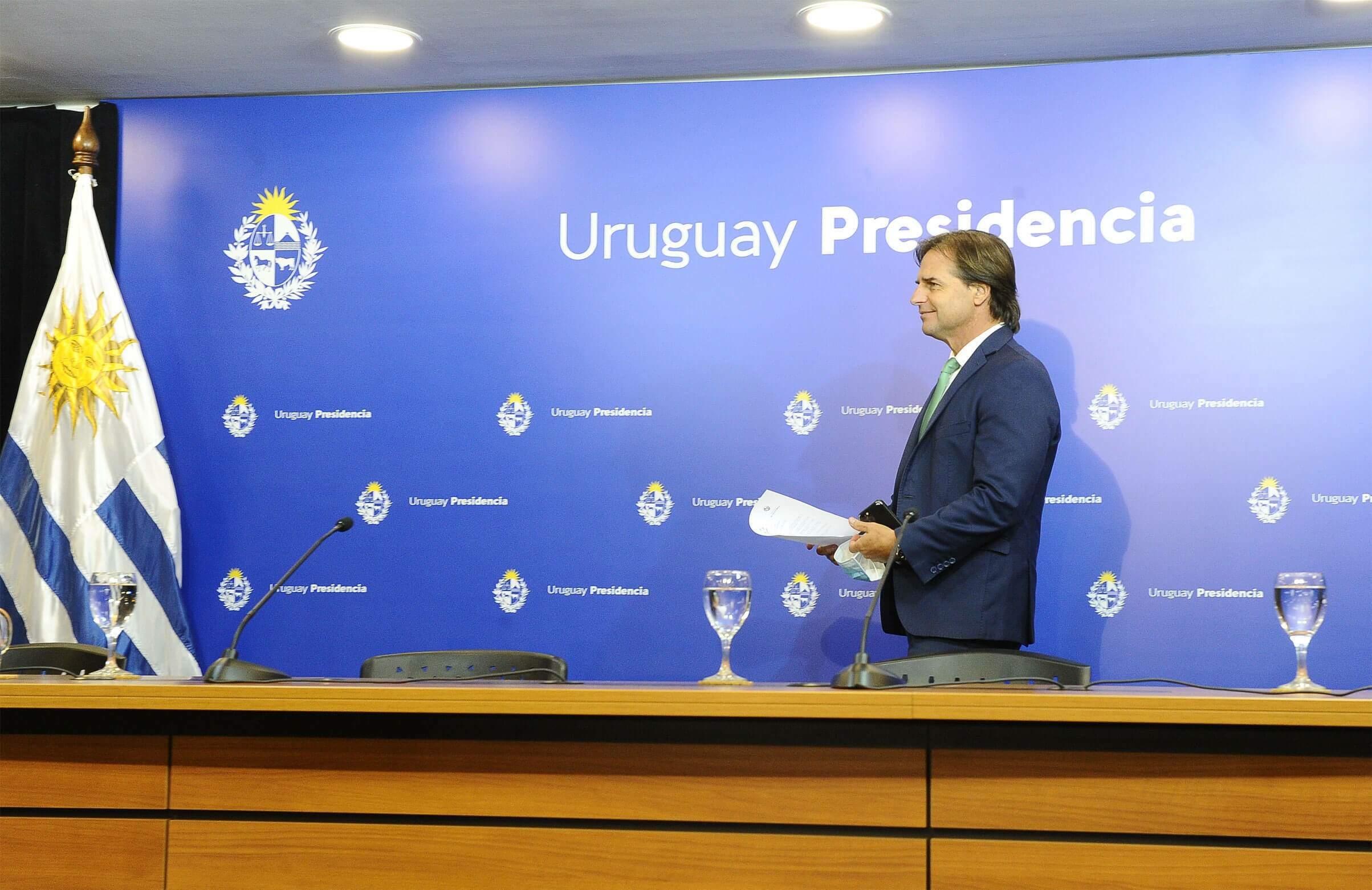 Na imagem, presidente do Uruguai em frente a painel azul em coletiva de imprensa. Conteúdo sobre sistema eleitoral no Uruguai.
