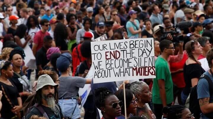 """Na imagem, manifestantes e uma mulher segurando uma placa """"our lives begin to end the day we becomes silent about what matters"""". Conteúdo sobre Discurso de ódio."""