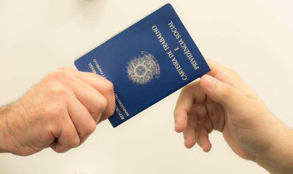 na imagem, duas mãos segurando uma carteira de trabalho. Conteúdo sobre Contrato verde e amarelo