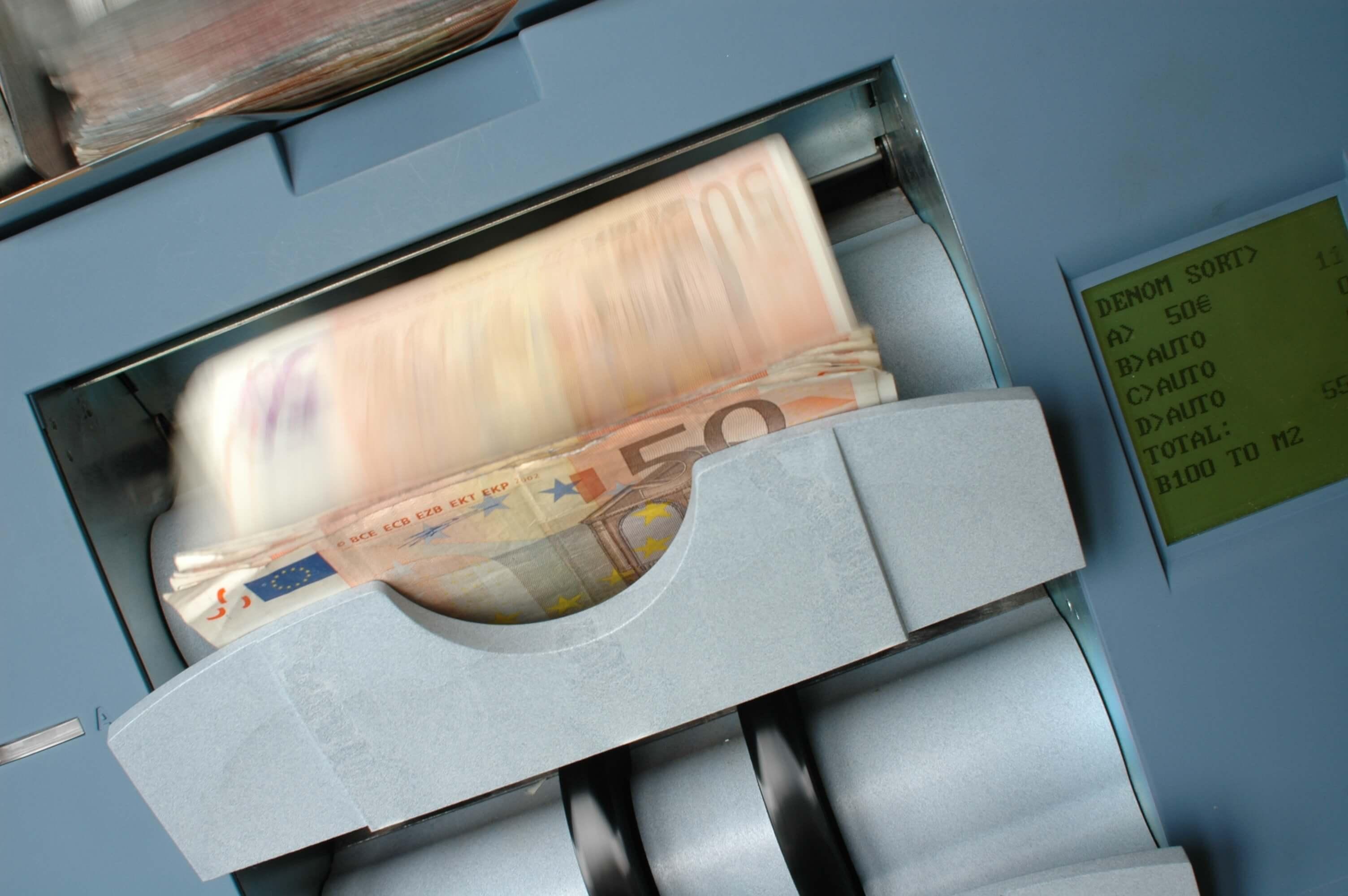 notas de dinheiro sendo contadas em máquina. conteúdo sobre armadilha da liquidez