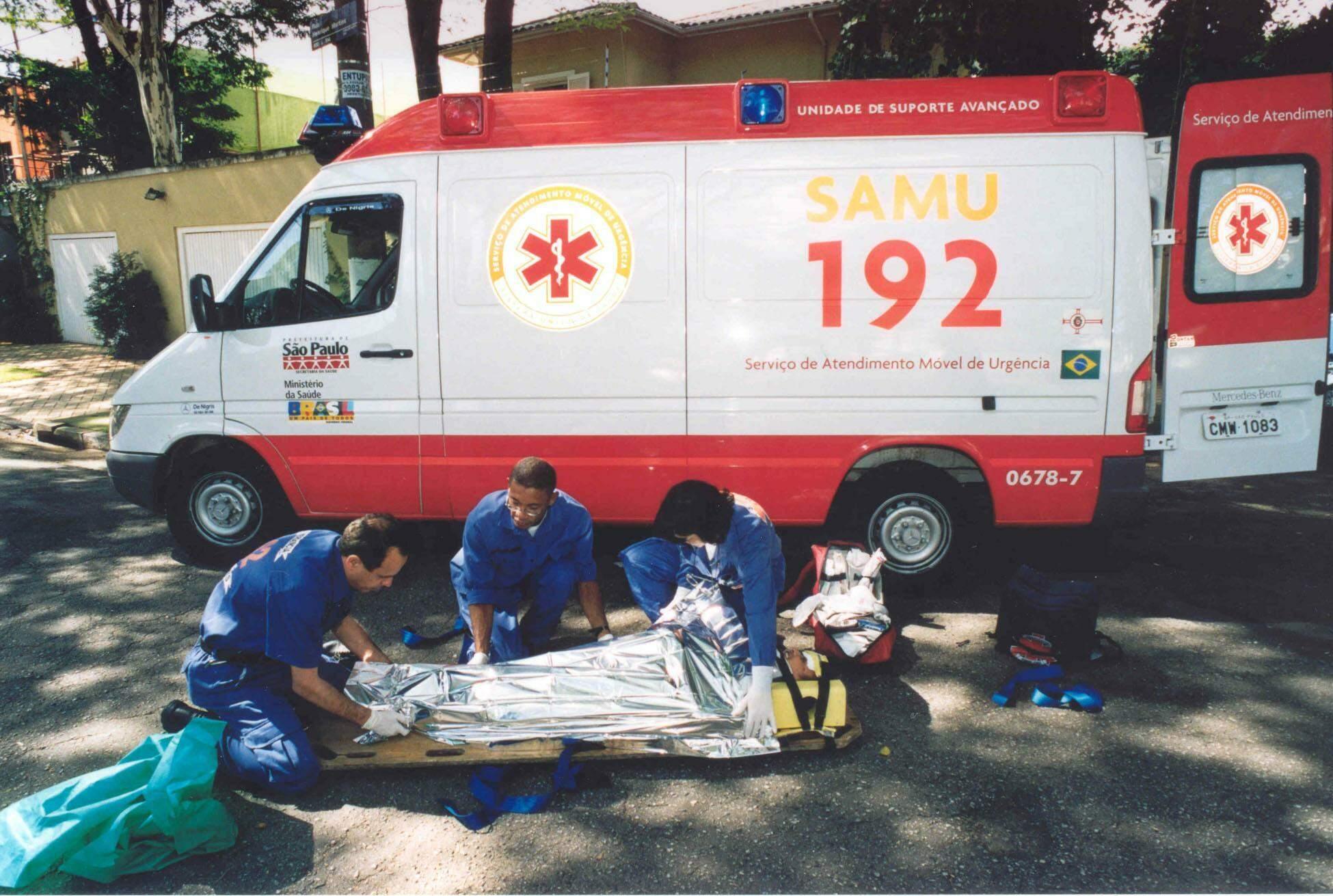 Foto de paramédicos e ambulância do Samu.
