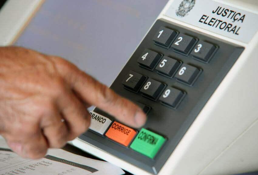 Pessoa confirmando o voto em urna eletrônica. Conteúdo sobre adiamento das eleições 2020.