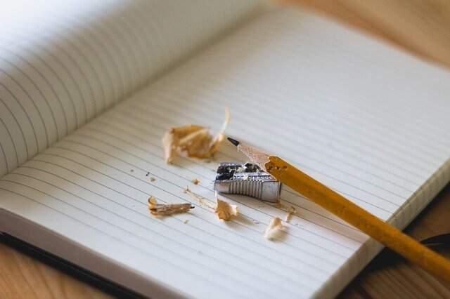 Imagem de um lápis, que foi apontado sobre a superfície de um caderno.